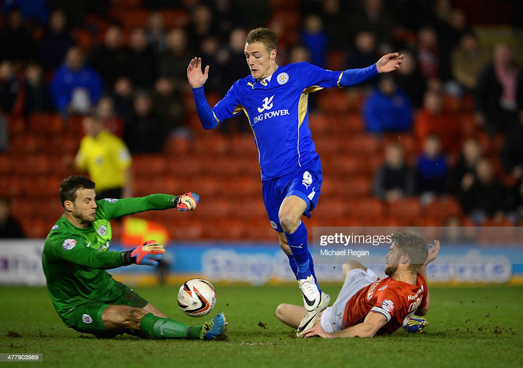 Jamie Vardy of Leicester is challenged by Luke Steele and Martin Cranie of Barnsley during the Sky Bet Championship match between Barnsley and Leicester City at Oakwell on March 11, 2014 in Barnsley, England,