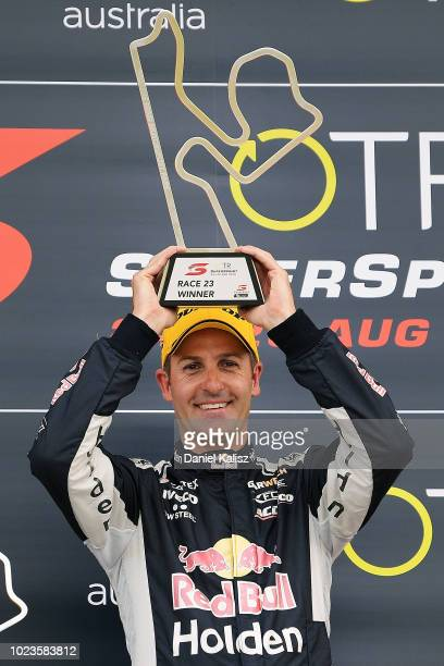 Jamie Whincup driver of the Red Bull Holden Racing Team Holden Commodore ZB celebrates on the podium after winning race 23 for the Supercars...