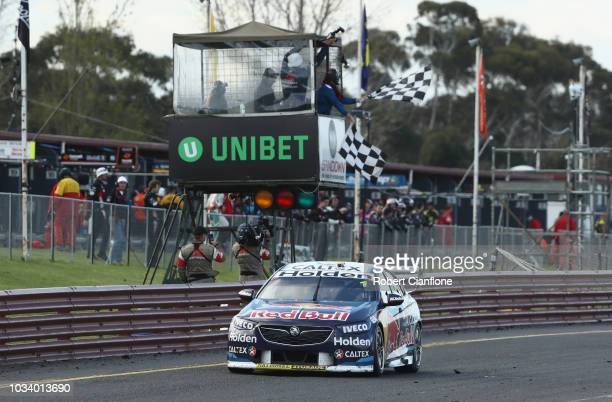 Jamie Whincup driver of the Red Bull Holden Racing Team Holden Commodore ZB crosses the line to win the Sandown 500 at Sandown International Motor...