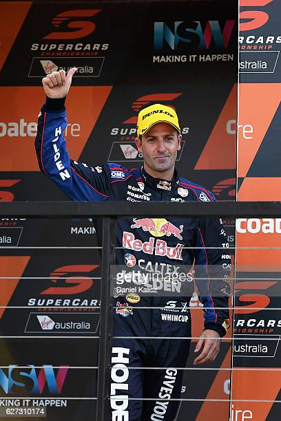 Jamie Whincup driver of the Red Bull Racing Australia Holden Commodore VF reacts on the podium after winning race 28 for the Sydney 500 which is part...