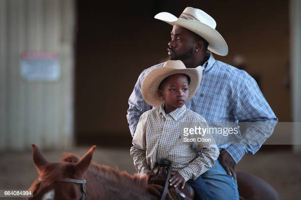 Jamil Hunt shares a saddle with his sixyearold son Jamil Hunt Jr as they prepare to ride into the arena for the start of competition at the Bill...