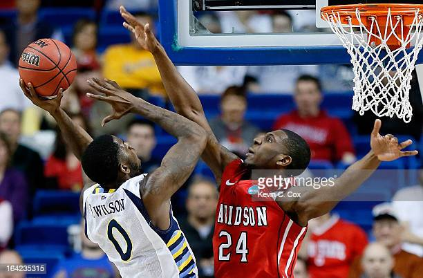 Jamil Wilson of the Marquette Golden Eagles shoots against De'Mon Brooks of the Davidson Wildcats in the second half during the second round of the...