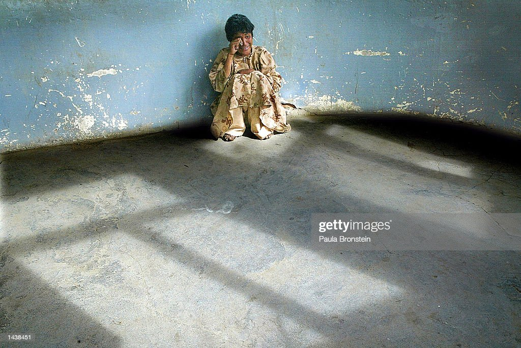 Jamila, 35, talks to herself in an empty room at the Kabul women's mental institution, home for the mentally ill, September30, 2002 in Kabul, Afghanistan. The home where 28 females live is part of Marastoon, a housing complex for Afghan's handicapped run by the Afghan Red Crescent Society. It has no running water or medical facility. After two decades of war Afghanistan is struggling to find the funds to help their most vulnerable people.