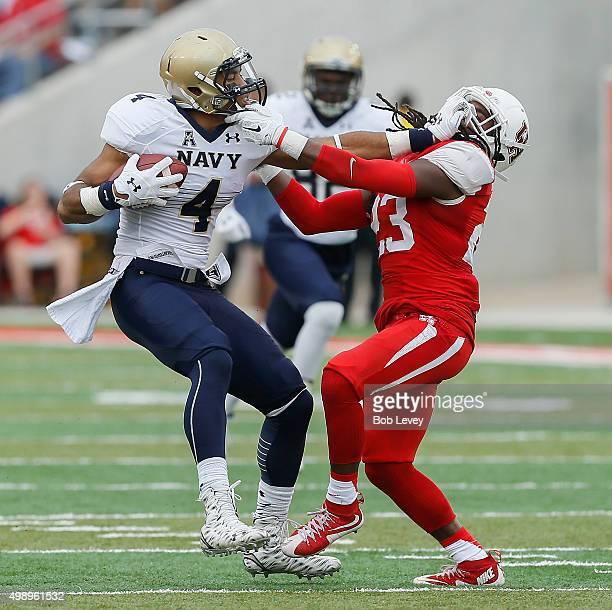 Jamir Tillman of the Navy Midshipmen gives Trevon Stewart of the Houston Cougars a stiff arm after a reception at TDECU Stadium on November 27 2015...