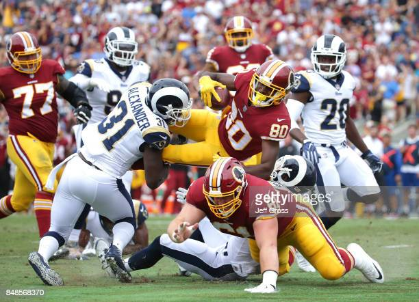 Jamison Crowder of the Washington Redskins goes airborne as Maurice Alexander of the Los Angeles Rams defends during the first quarter at Los Angeles...