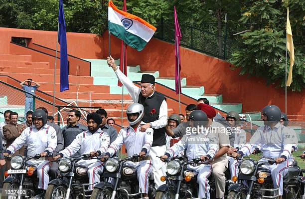 Jammu and Kashmir Chief Minister Dr Farooq Abdullah carries a flag while riding on the back of a motorcycle during India's official Independence Day...