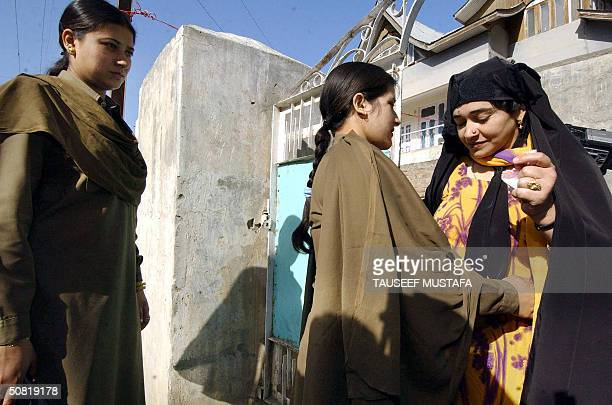 Jammu and Kashmir policewomen frisk a Kashmiri Muslim woman as she enters a polling station to cast her vote in Doda some 200 kilometres south of...