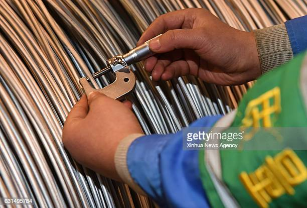 TAIYUAN Jan 11 2017 A worker measures steel components for pen tips at Taiyuan Iron and Steel or TISCO in Taiyuan north China's Shanxi Province Jan...