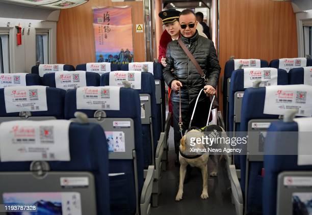 Jan. 14, 2020-- Guide dog Xiaoqi and its handler take the G6647 bullet train at Zhengzhoudong Railway Station in Zhengzhou, central China's Henan...