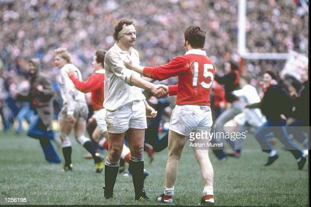 Bill Beaumont of England shakes hands with his opposing number JPR Williams of Wales at the end of the Five Nations match at Cardiff Arms Park in...