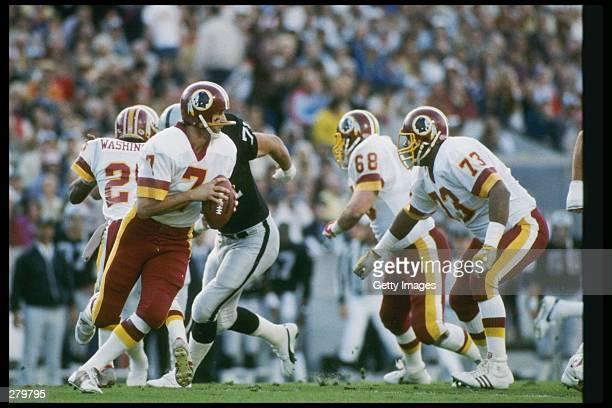 Quarterback Joe Theismann of the Washington Redskins looks to pass the ball during Super Bowl XVIII against the Los Angeles Raiders at Tampa Stadium...