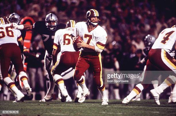 Quarterback Joe Theismann of the Washington Redskins rolls out during the Redskins 389 loss to the Los Angeles Raiders in Super Bowl XVIII at Tampa...