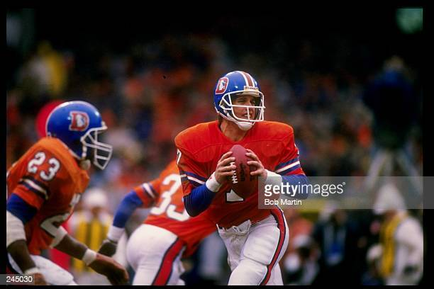 Quarterback John Elway of the Denver Broncos drops back to pass during the AFC Championship Game against the Cleveland Browns at Cleveland Stadium in...