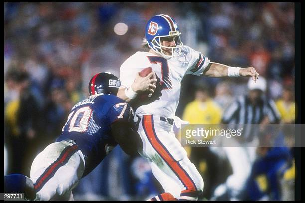 Quarterback John Elway of the Denver Broncos is being rushed by defensive lineman Leonard Marshall of the New York Giants at Super Bowl XXI at the...