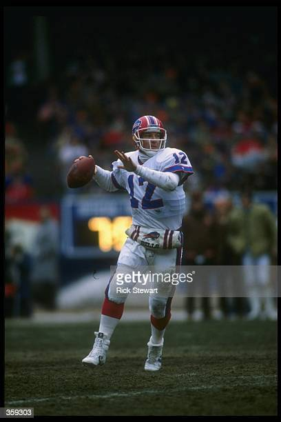 Quarterback Jim Kelly of the Buffalo Bills looks to pass the ball during a playoff game against the Cleveland Browns at Cleveland Stadium in...