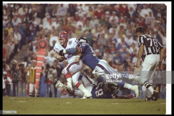 Quarterback Jim Kelly of the Buffalo Bills is sacked by a New York Giants player during Super Bowl XXV at Tampa Stadium in Tampa Florida The Giants...