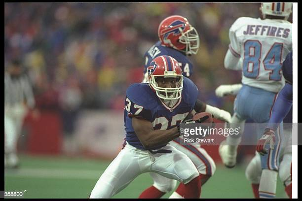 Defensive back Nate Odomes of the Buffalo Bills runs with the ball after making an interception during a playoff game against the Houston Oilers at...