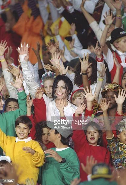 Entertainer Michael Jackson is surrounded by children during the Super Bowl XXVII game between the Buffalo Bills and the Dallas Cowboys at the Rose...