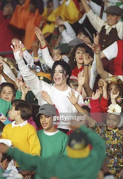 Entertainer Michael Jackson is surrounded by children during the Super Bowl XXVII game between the Buffalo Bills and Dallas Cowboys at the Rose Bowl...