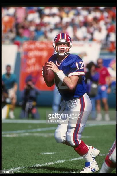 Quarterback Jim Kelly of the Buffalo Bills looks to throw the ball during a playoff game against the Miami Dolphins at Rich Stadium in Orchard Park,...