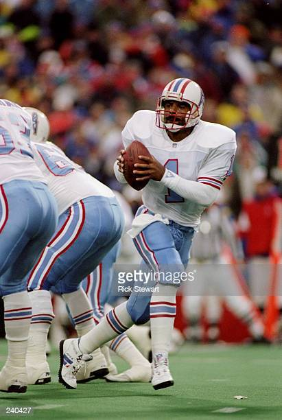 Quarterback Warren Moon of the Houston Oilers scrambles with the ball during a game against the Buffalo Bills at Rich Stadium in Orchard Park New...