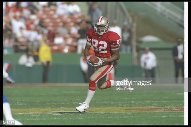 Wide receiver John Taylor of the San Francisco 49ers moves the ball during a playoff game against the New York Giants at Candlestick Park in San...