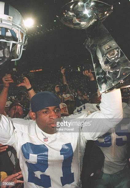 Cornerback Deion Sanders of the Dallas Cowboys holds up the Vince Lombardi Trophy following the Cowboys 2717 victory over the Pittsburgh Steelers in...