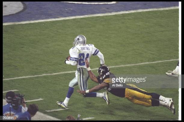 Defensive back Larry Brown of the Dallas Cowboys returns an interception for a touchdown as Pittsburgh Steelers running back John Williams tries to...