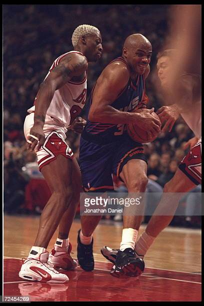 Forward Charles Barkley of the Phoenix Suns drives between guard Dennis Rodman and center Luc Longley of the Chicago Bulls at the United Center in...