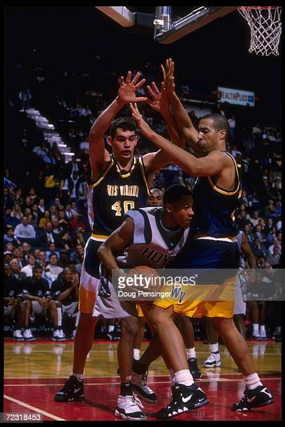 Guard Allen Iverson of the Georgetown Hoyas is doubleteamed by center Leon Agnew and Sandro Varejaoas he ties to take the ball downcourt Iverson...