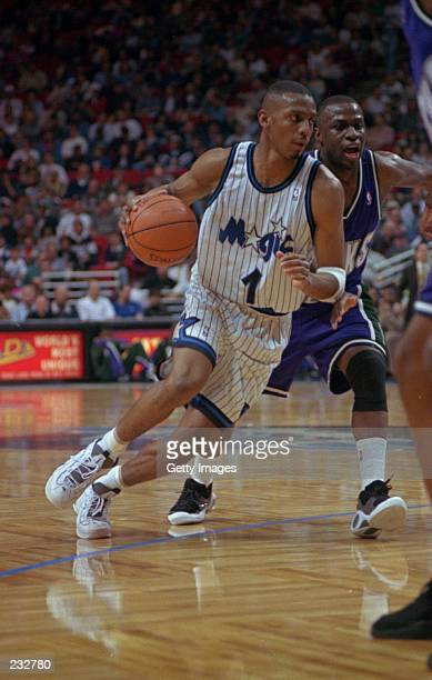 Point guard Anfernee Hardaway of the Orlando Magic dribble drives around guard Sherman Douglas of the Milwaukee Bucks during the Magic''s 9388...