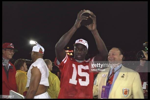 Quarterback Tommie Frazier of the Nebraska Cornhuskers holds the trophy aloft after his team defeated the Florida Gators in the Fiesta Bowl at Sun...