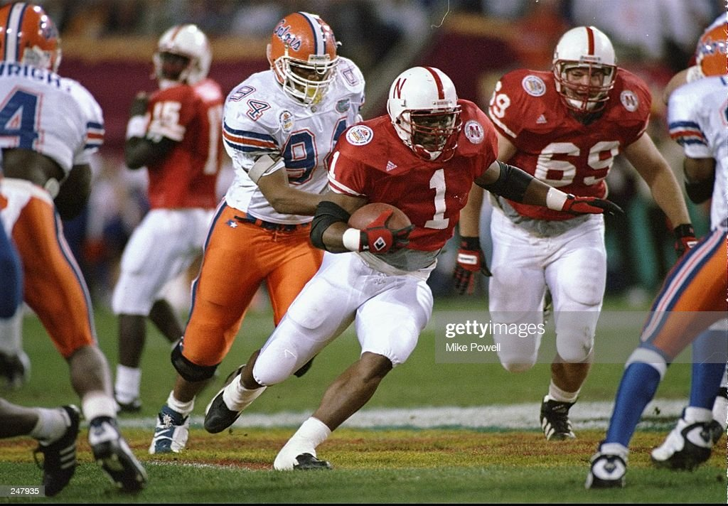 Running back Lawrence Phillips of the Nebraska Cornhuskers runs with the ball and is chased by defensive tackle Larry Townsand of the Florida Gators during the Fiesta Bowl game at Sun Devil Stadium in Tempe, Arizona. Florida won the game 24-12