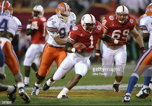 Running back Lawrence Phillips of the Nebraska Cornhuskers runs with the ball and is chased by defensive tackle Larry Townsand of the Florida Gators...