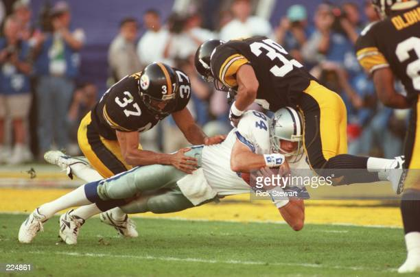 Tight end Jay Novacek of the Dallas Cowboys is tackled by cornerback Carnell Lake and safety Darren Perry of the Pittsburgh Steelers during the first...