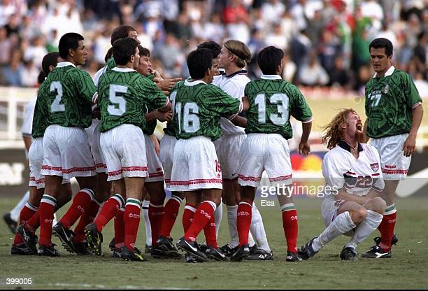 Alexi Lalas of the USA goes down in pain after a foul by Luis Roberto Alves of Mexico in the US Cup match at the Rose Bowl in Pasadena California USA...