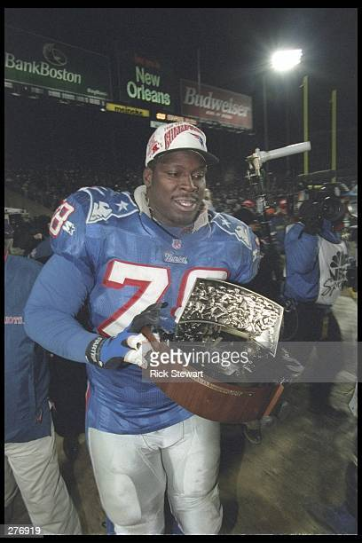 Defensive lineman Bruce Armstrong of the New England Patriots proudly holds the Lamar Hunt trophy defeating the Jacksonville Jaguars in the AFC...