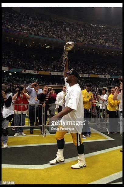 Defensive lineman Reggie White of the Green Bay Packers celebrates with the Vince Lombardi trophy after Super Bowl XXXI against the New England...