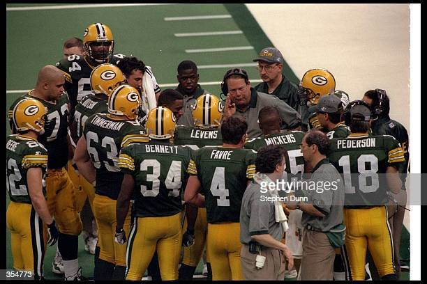 Green Bay Packers head coach Mike Holmgren confers with his team during Super Bowl XXXI against the New England Patriots at the Superdome in New...