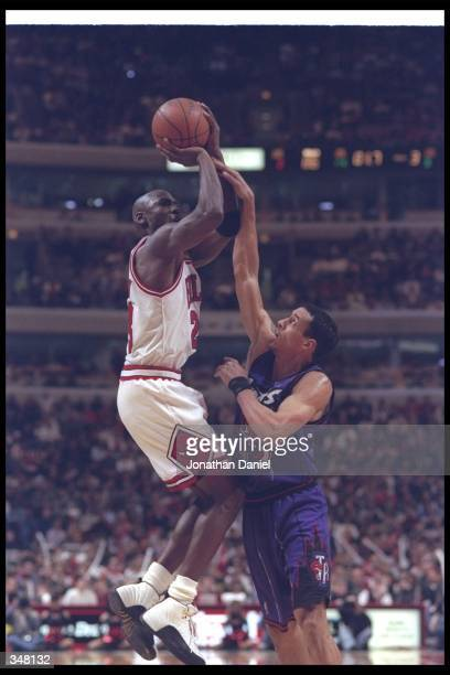 Guard Michael Jordan of the Chicago Bulls takes a shot as Toronto Raptors guard Doug Christie covers him during a game at the United Center in...