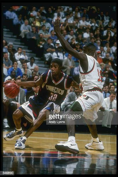 Guard Richard Hamilton of the Connecticut Huskies moves the ball as Miami Hurricanes guard Clifton Clark covers him during a game at the Miami Arena...
