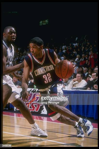 Guard Richard Hamilton of the Connecticut Huskies moves the ball as Georgetown Hoyas forward Jahidi White covers him during a game at the USAir Arena...