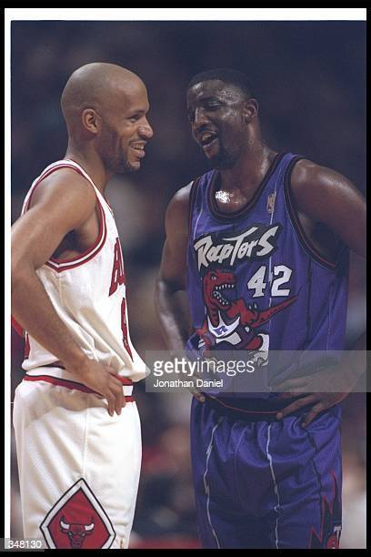 Guard Ron Harper of the Chicago Bulls and Toronto Raptors forward Walt Williams confer during a game at the United Center in Chicago Illinois The...
