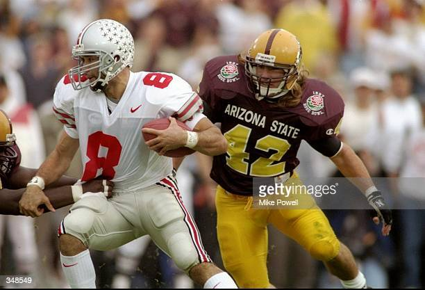 Quarterback Stanley Jackson of the Ohio State Buckeyes moves the ball as Arizona State Sun Devils linebacker Pat Tillman chases him during the Rose...