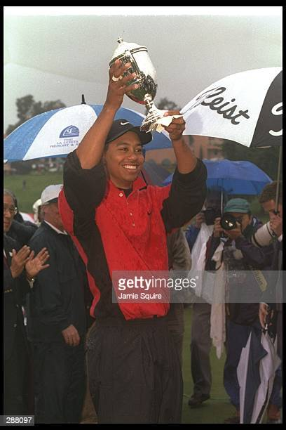 Tiger Woods holds his trophy triumphantly during the Mercedes Championships at La Costa Resort in Carlsbad California Mandatory Credit Jamie Squire...