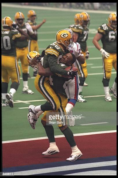 Wide receiver Andre Rison and teammate Antonio Freeman of the Green Bay Packers celebrate in the endzone after Rison caught a 54 yard touchdown pass...