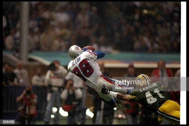 Wide receiver Terry Glenn of the New England Patriots catches the ball as Green Bay Packers defensive back Eugene Robinson tackles him during Super...