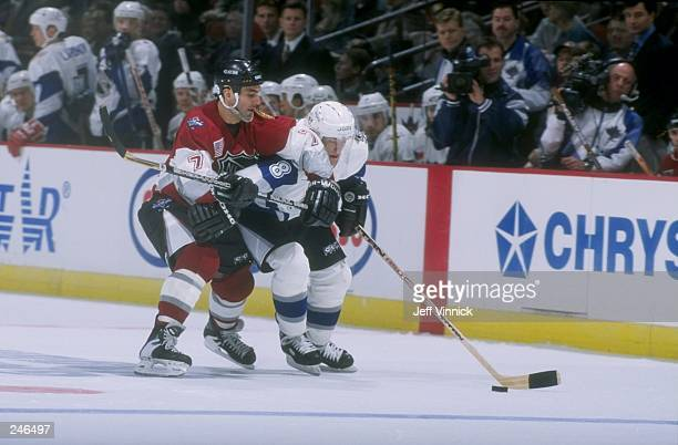 Chris Chelios of team North America battles Teemu Selanne of team World for the puck during the 1998 NHL AllStar Game at General Motors Palace in...