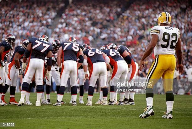 Defensive end Reggie White of the Green Bay Packers looks on as the Denver Broncos huddle during the Packers 31-24 loss in Super Bowl XXXII at...