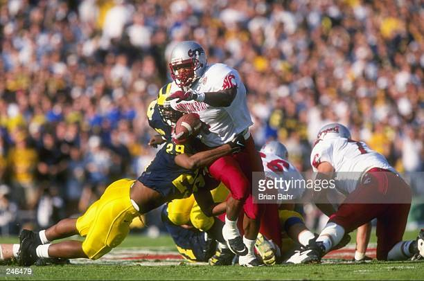 Running back Michael Black of Washington State tries to escape the grasp of Marcus Ray of Michigan during the Cougars 2116 loss to Michigan in the...